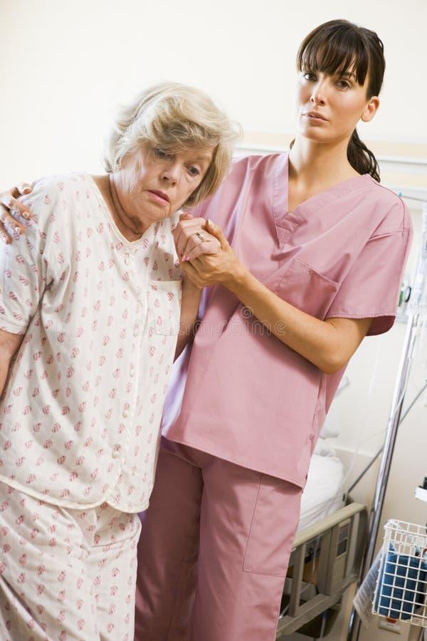 Enfermera que ayuda a la mujer mayor a recorrer fotografía de archivo