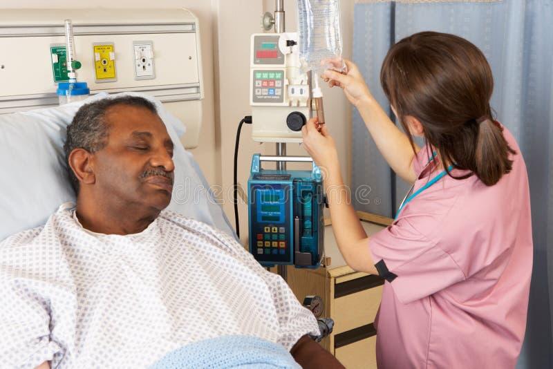 Enfermera que controla el goteo del IV del paciente mayor en sala fotografía de archivo