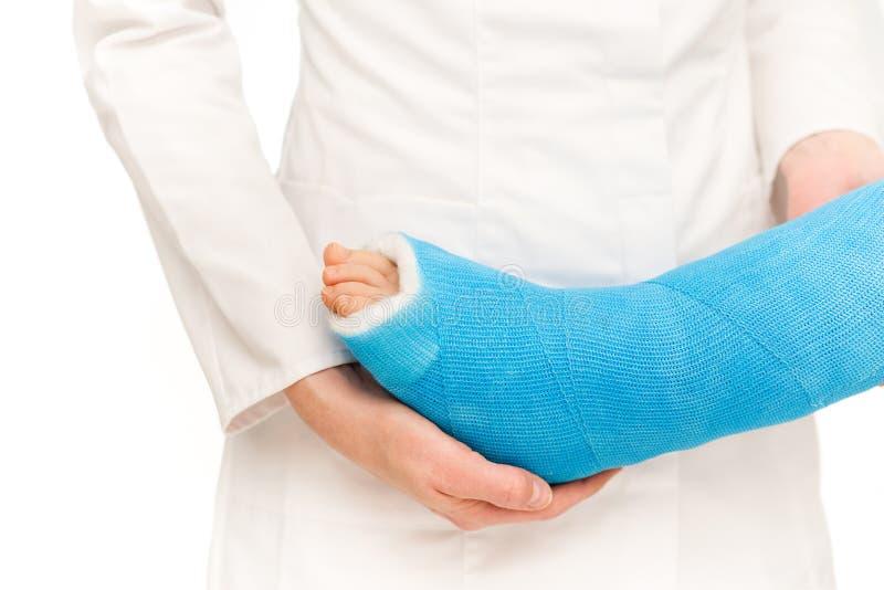 Enfermera que cuida que toma cuidado de poca pierna quebrada del niño imagenes de archivo