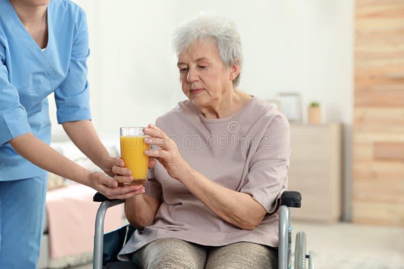 Enfermera que da el vidrio de jugo a la mujer mayor en silla de ruedas Ayuda de gente mayor foto de archivo libre de regalías