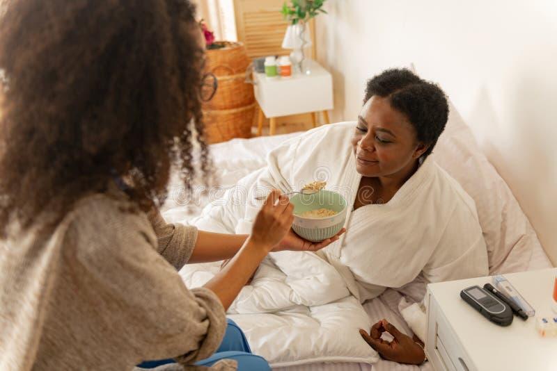 Enfermera que da un poco de gachas de avena para la mujer que miente en cama despu?s de cirug?a foto de archivo