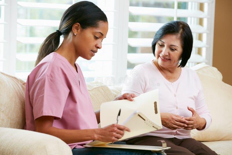 Enfermera que discute expedientes con el paciente femenino mayor imagenes de archivo
