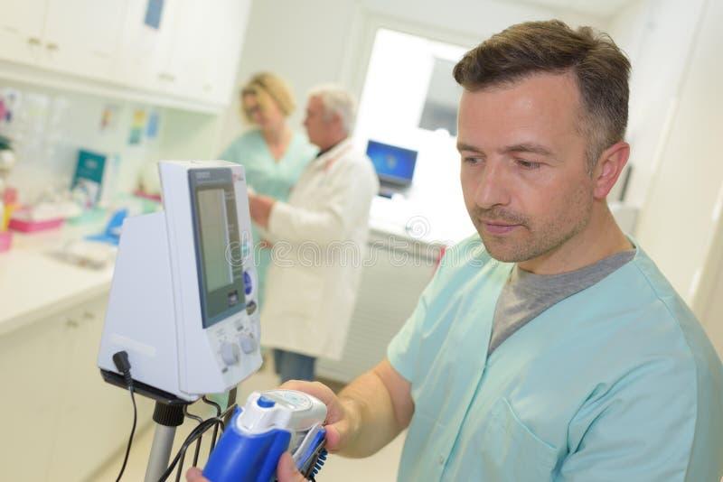Enfermera que examina el equipo de supervisión imagenes de archivo