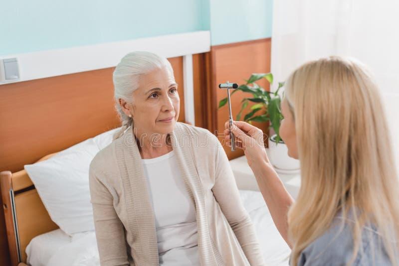 enfermera que examina a la mujer mayor con el martillo reflejo fotos de archivo libres de regalías