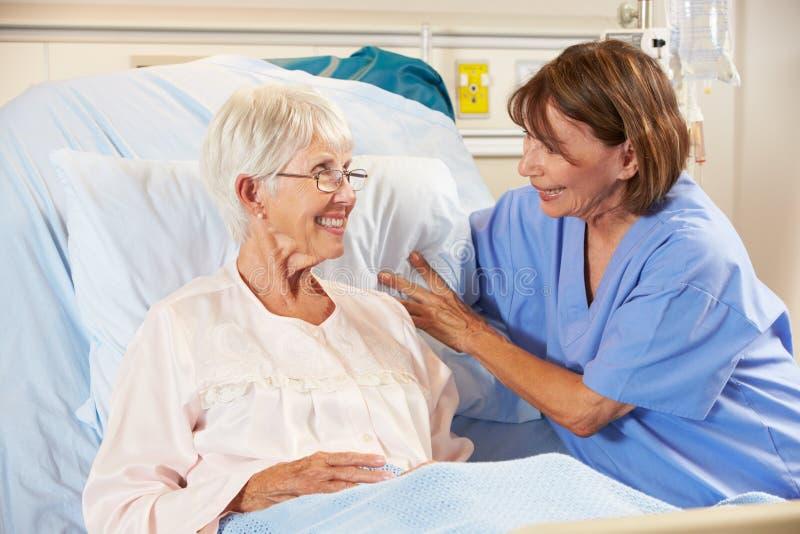 Enfermera que habla con el paciente femenino mayor en cama de hospital imagenes de archivo