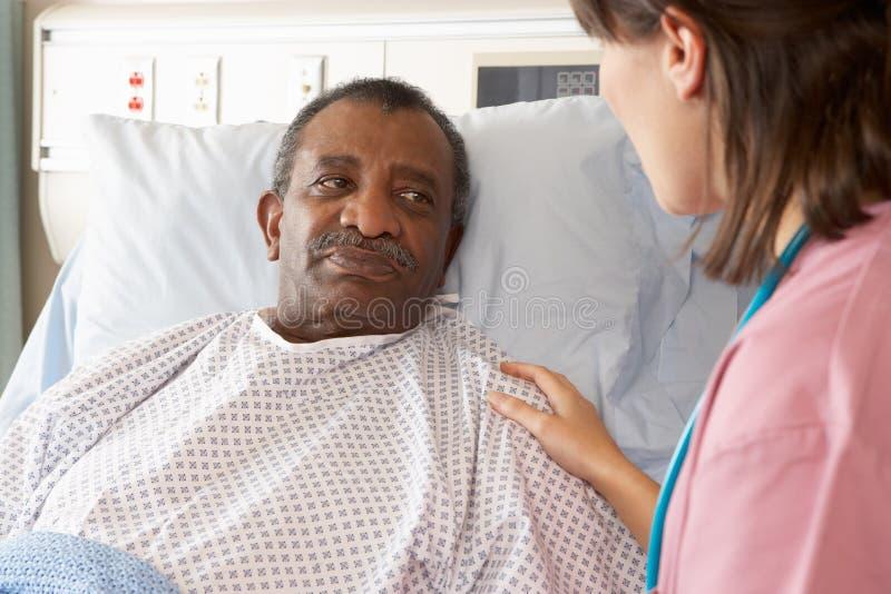Enfermera que habla con el paciente masculino en sala fotografía de archivo