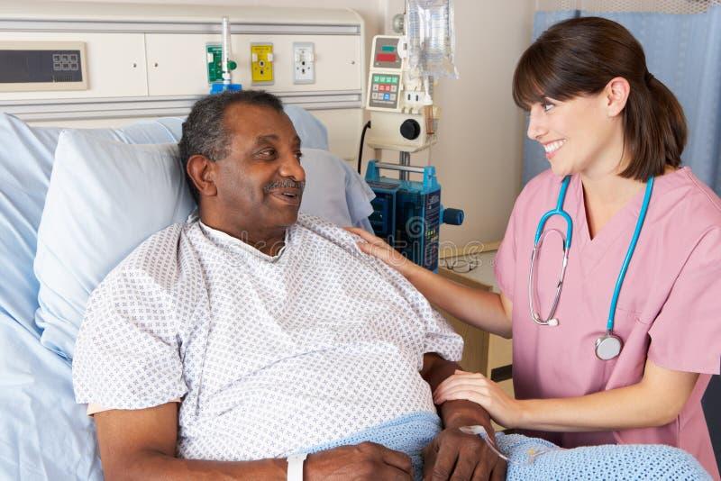 Enfermera que habla con el paciente masculino mayor en sala fotos de archivo libres de regalías