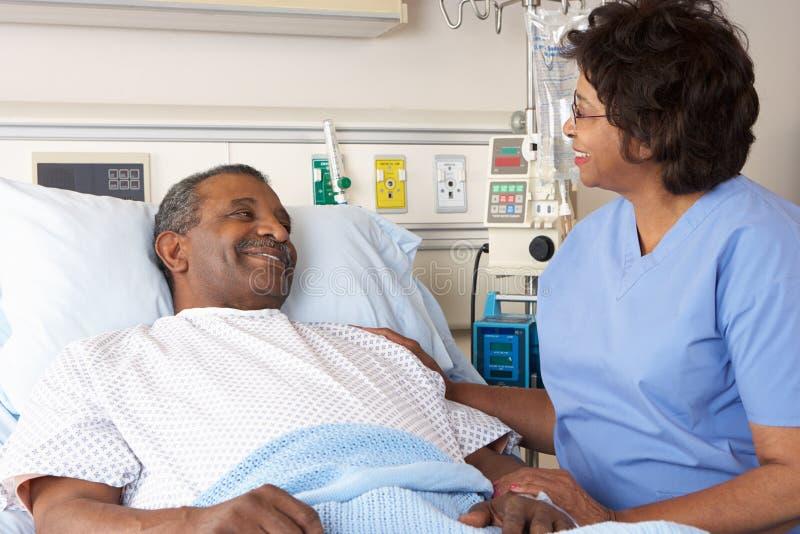 Enfermera que habla con el paciente masculino mayor en sala foto de archivo