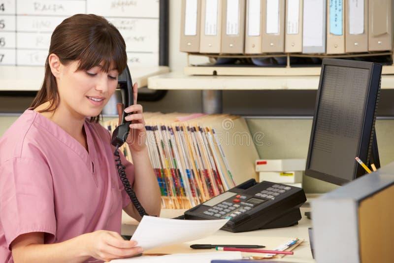Enfermera que hace llamada de teléfono en la estación de las enfermeras fotos de archivo libres de regalías