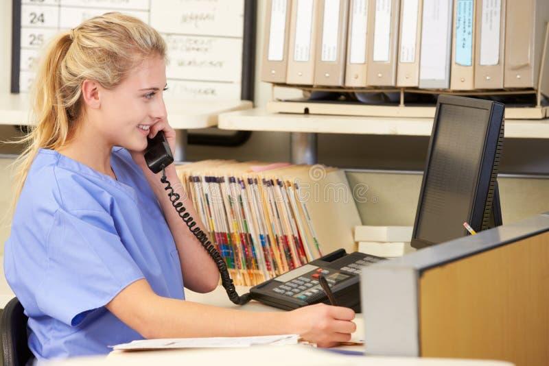 Enfermera que hace llamada de teléfono en la estación de las enfermeras imagen de archivo