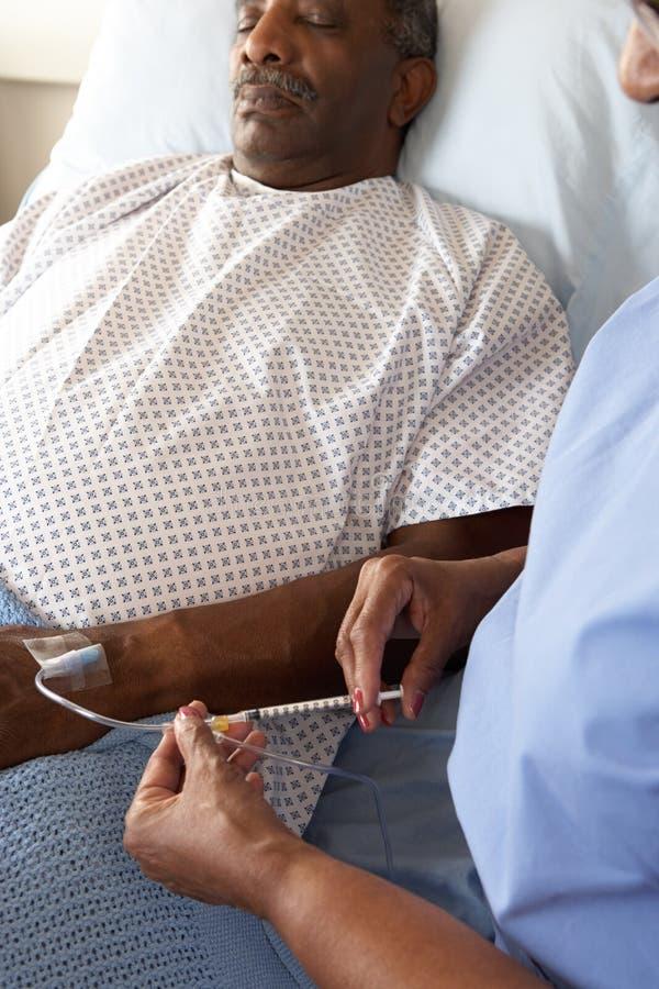 Enfermera que inyecta al paciente masculino mayor en cama de hospital fotos de archivo