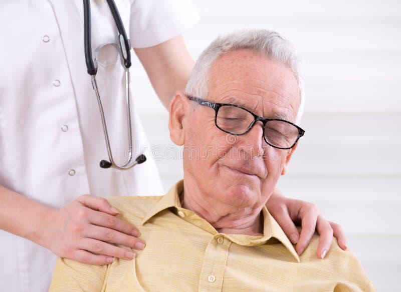 Enfermera que lleva a cabo las manos en hombros del viejo hombre foto de archivo libre de regalías
