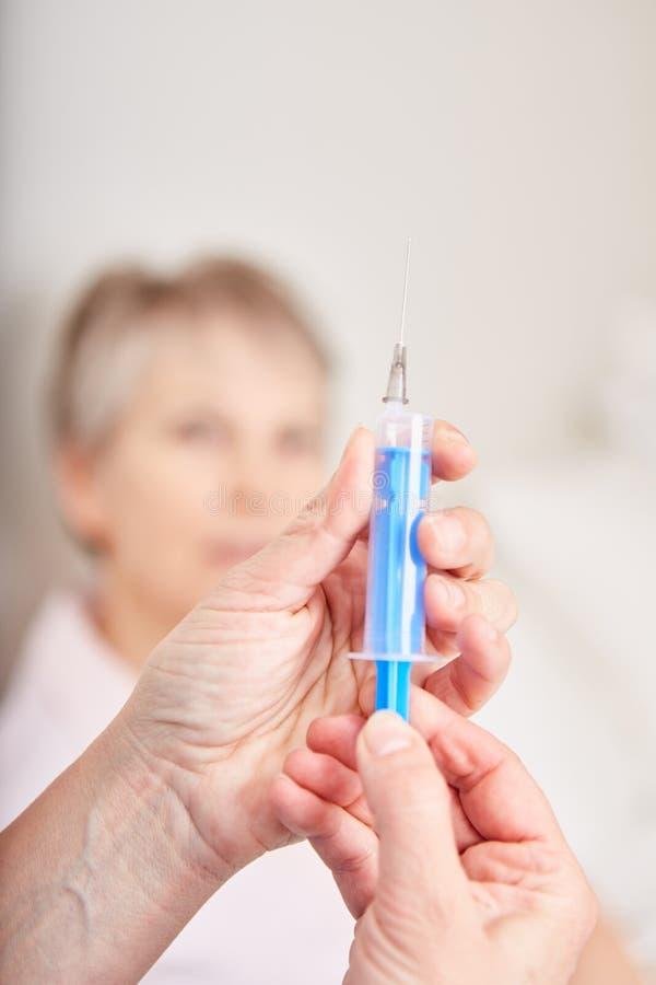 Enfermera que prepara la jeringuilla para la inyección imagenes de archivo