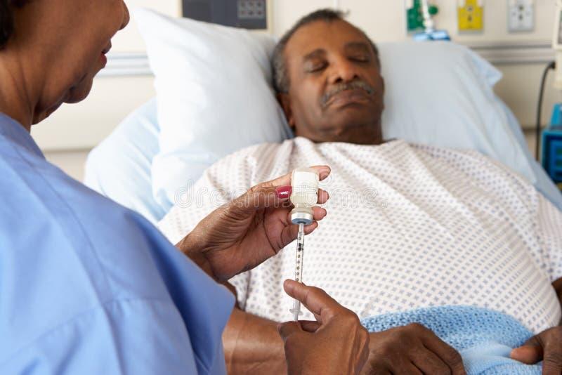 Enfermera que se prepara para dar la inyección paciente masculina mayor imagen de archivo