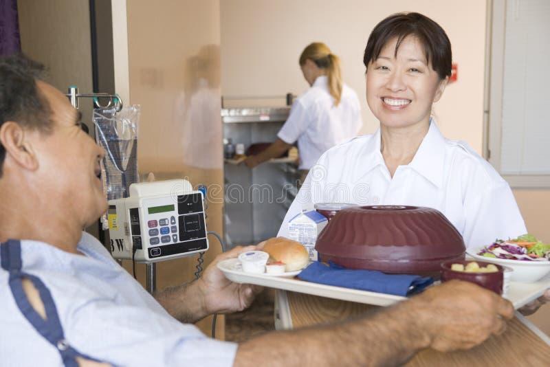 Enfermera que sirve a un paciente una comida en su cama foto de archivo