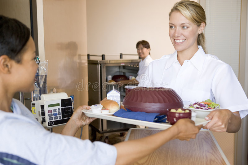 Enfermera que sirve a un paciente una comida en su cama fotografía de archivo
