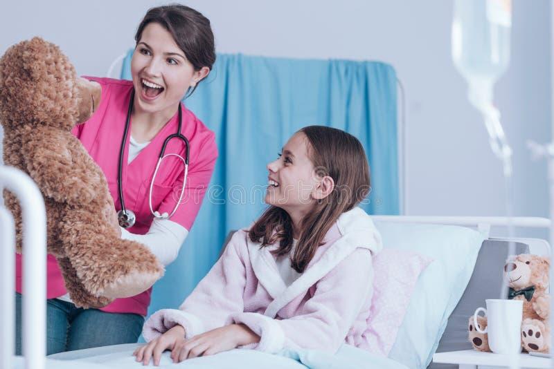 Enfermera que sostiene el oso de peluche imágenes de archivo libres de regalías