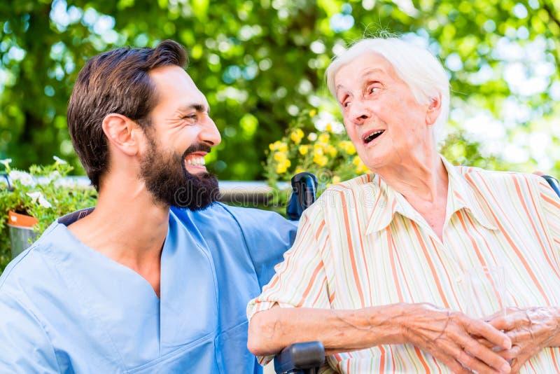 Enfermera que tiene charla con la mujer mayor en clínica de reposo imagen de archivo