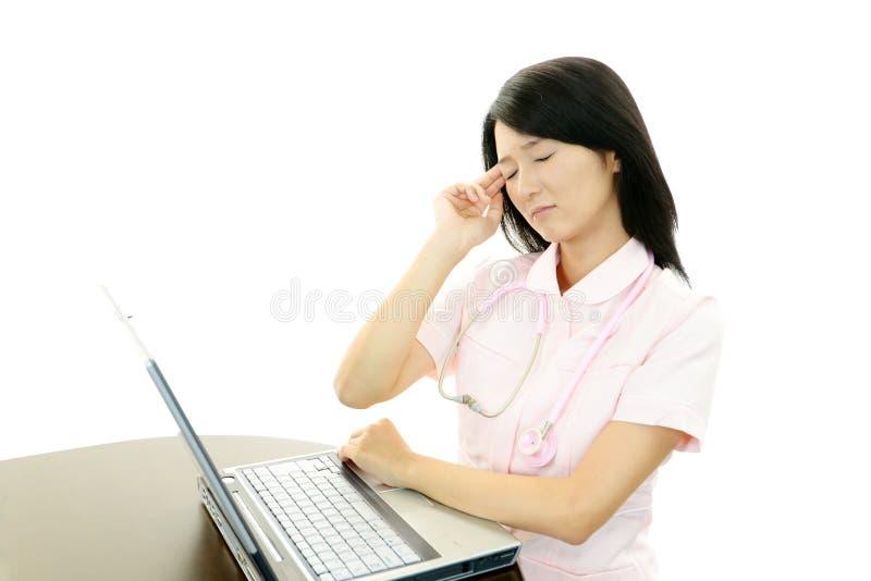 Enfermera que tiene un dolor de cabeza foto de archivo libre de regalías