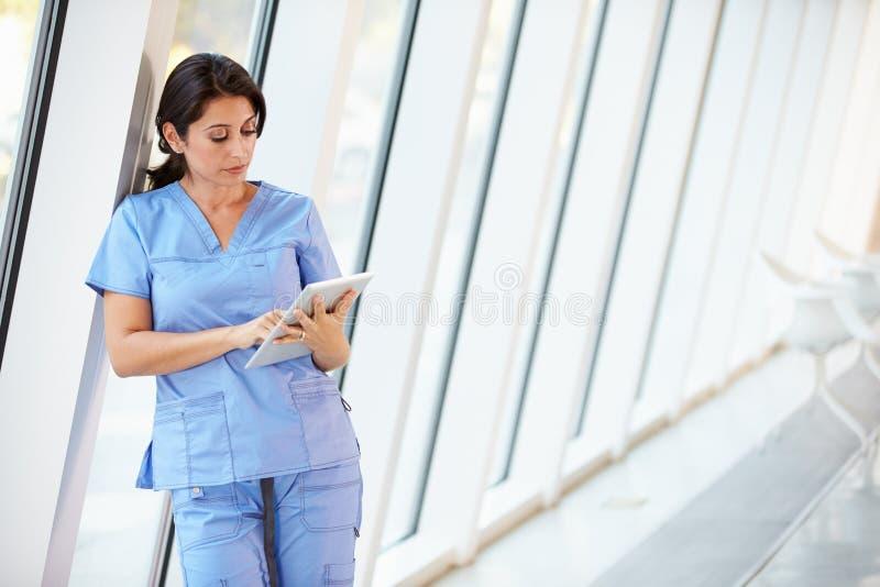 Enfermera que usa la tablilla de Digitaces en pasillo del hospital moderno imágenes de archivo libres de regalías