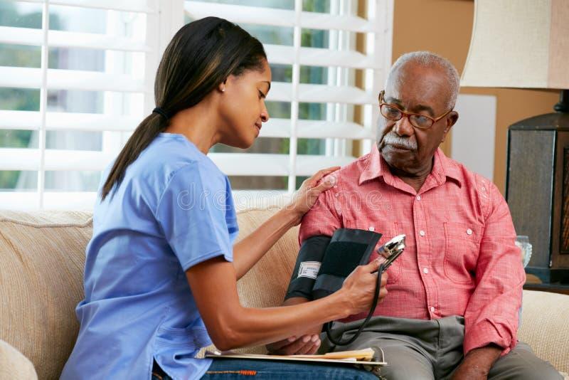 Enfermera que visita al paciente masculino mayor en casa foto de archivo