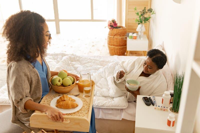 Enfermera rizada que cuida que trae la bandeja con el desayuno para el paciente fotos de archivo libres de regalías