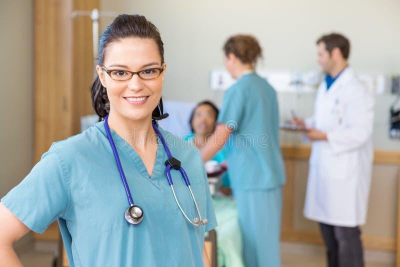 Enfermera Smiling Against Patient y Team In médico foto de archivo libre de regalías