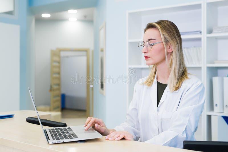 Enfermera sonriente con la cita de previsión del ordenador portátil para el paciente masculino en la recepción fotos de archivo