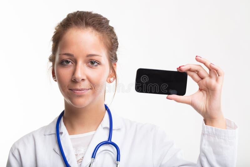 Enfermera sonriente de los jóvenes que sostiene un teléfono móvil fotografía de archivo