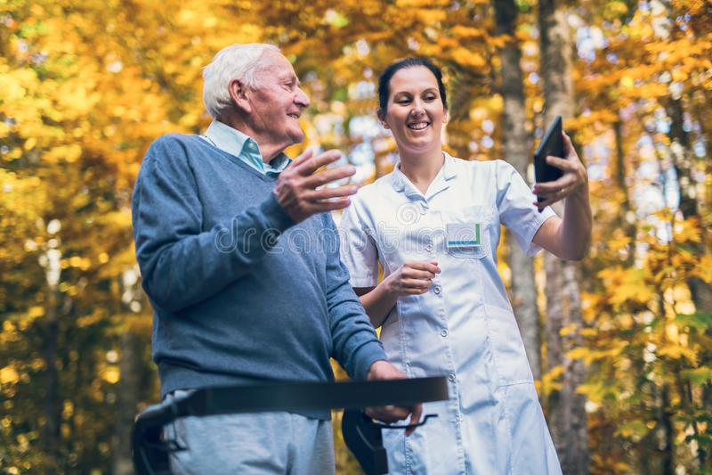 Enfermera sonriente del cuidador y paciente mayor inhabilitado en el caminante que usa la tableta digital imagenes de archivo