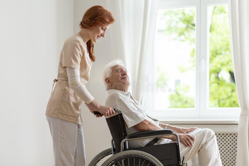 Enfermera sonriente que apoya al hombre mayor inhabilitado en la silla de ruedas imágenes de archivo libres de regalías