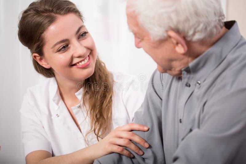 Enfermera sonriente que ayuda al hombre mayor imagen de archivo libre de regalías