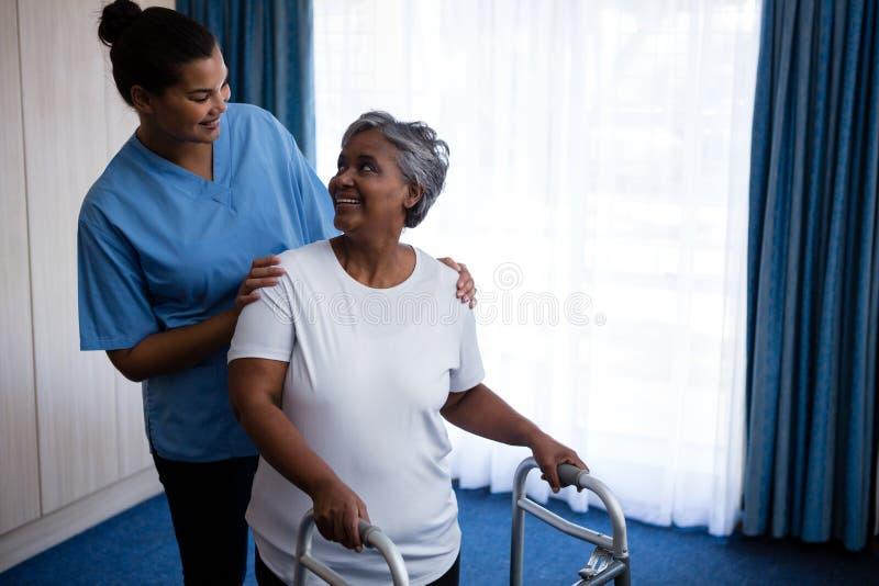 Enfermera sonriente que ayuda a la mujer mayor en caminar con el caminante imagenes de archivo