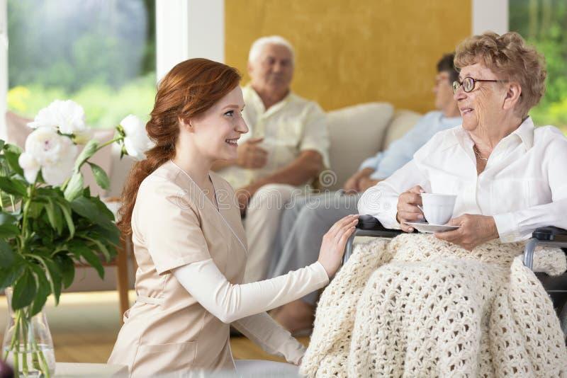 Enfermera sonriente que toma cuidado de la mujer mayor discapacitada en el nursin foto de archivo