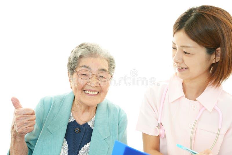 Enfermera sonriente y mujer mayor imagenes de archivo