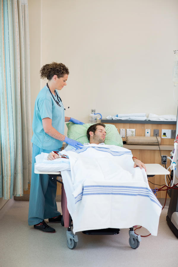 Enfermera Standing By Patient que recibe diálisis renal fotografía de archivo