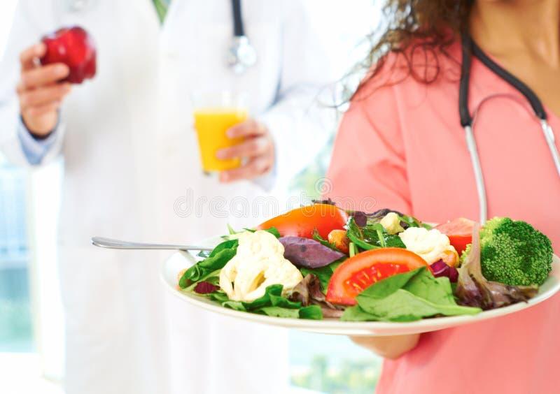 Enfermera y doctor con comida sana imagenes de archivo