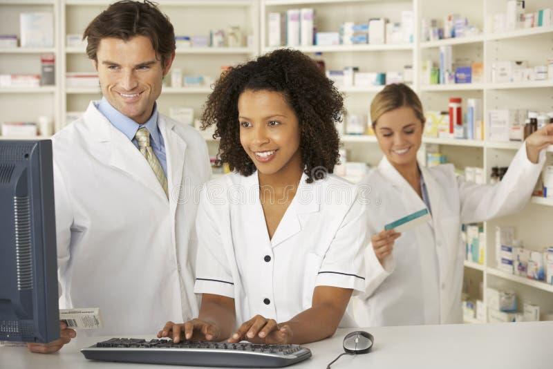 Enfermera y farmacéuticos que trabajan en farmacia fotos de archivo