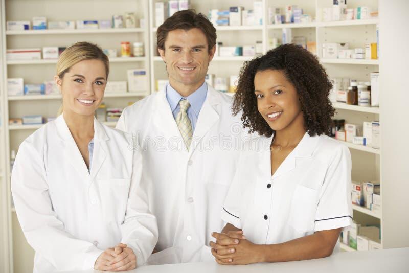Enfermera y farmacéuticos que trabajan en farmacia imagenes de archivo