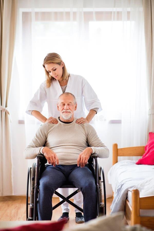 Enfermera y hombre mayor en silla de ruedas durante la visita casera imagen de archivo
