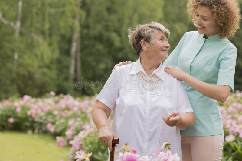 Enfermera y mujer mayor con un bastón en un jardín imagenes de archivo