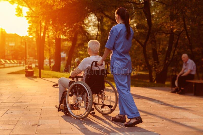 Enfermera y viejo hombre que se sienta en una silla de ruedas que mira la puesta del sol en el parque imágenes de archivo libres de regalías
