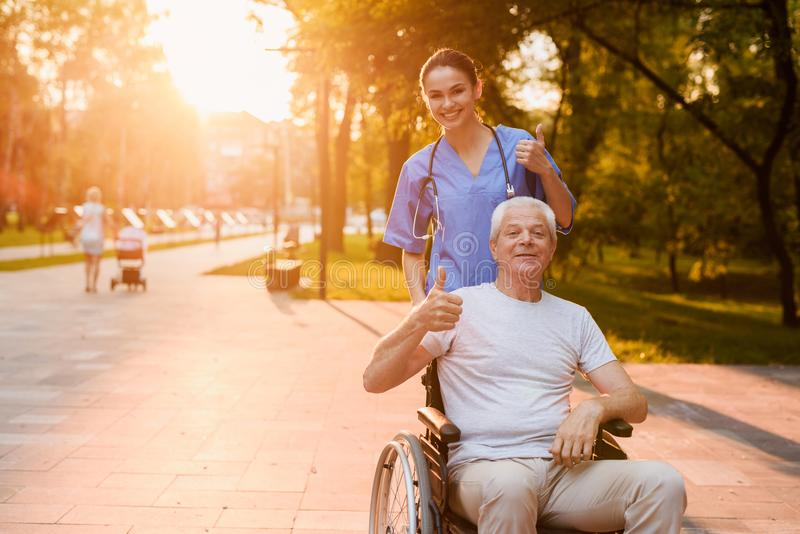 Enfermera y viejo hombre que sienta en mostrar de la silla de ruedas los pulgares para arriba en el parque en la puesta del sol foto de archivo libre de regalías