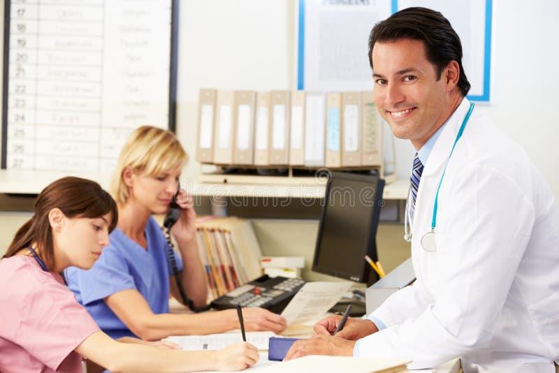 Enfermeras del doctor With dos que trabajan en la estación de las enfermeras imágenes de archivo libres de regalías