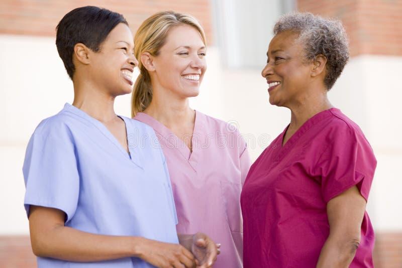 Enfermeras que se colocan fuera de un hospital fotografía de archivo libre de regalías