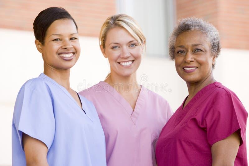 Enfermeras que se colocan fuera de un hospital foto de archivo