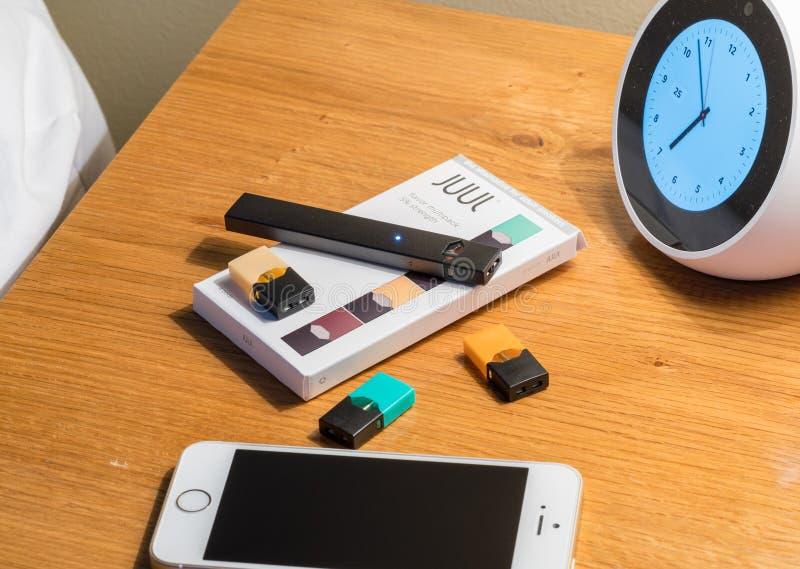 Enfermez dans une boîte tenir le distributeur et les cosses de nicotine de JUUL sur la table de chevet image stock