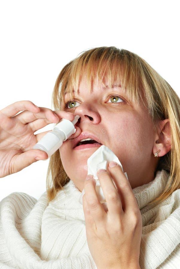 Enfermo con una medicina de la nariz del goteo de la mujer de la rinitis aislada fotos de archivo