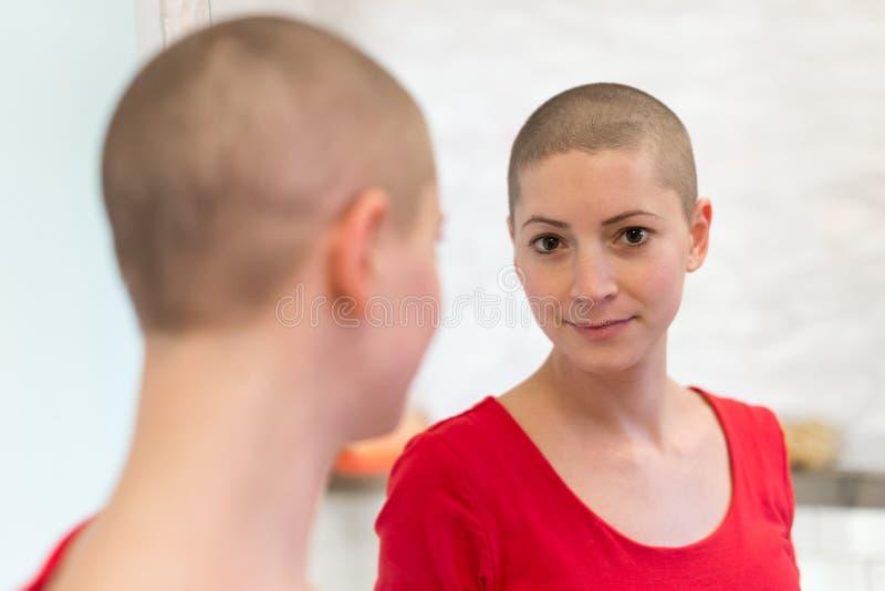 Enfermo de cáncer joven de la hembra adulta que mira en el espejo, sonriendo foto de archivo libre de regalías