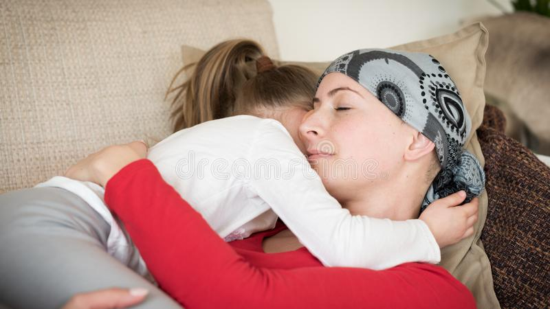 Enfermo de cáncer joven de la hembra adulta que pasa tiempo con su hija en casa, relajándose en el sofá imagenes de archivo
